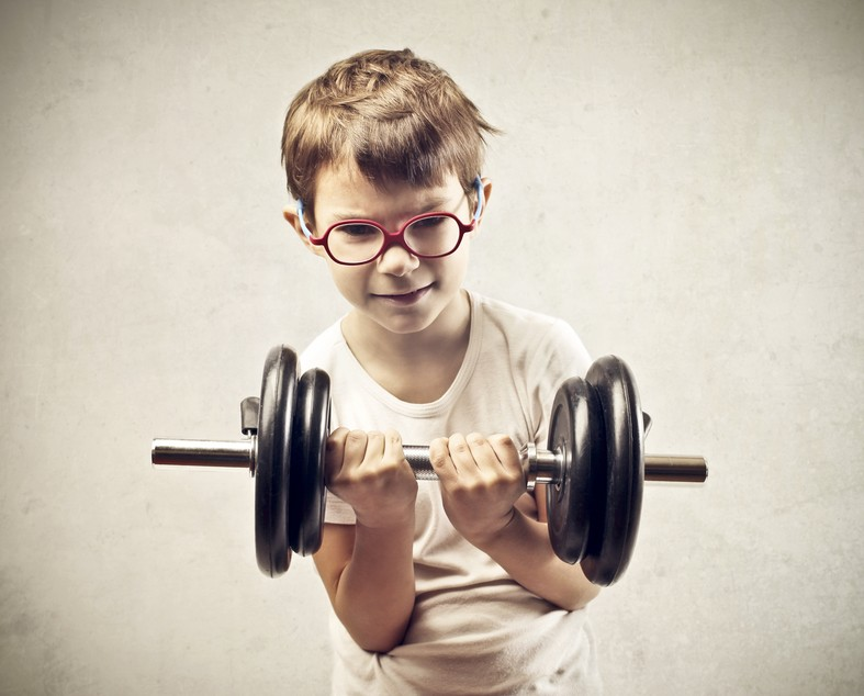 Little boy with classes lifting a dumbbell