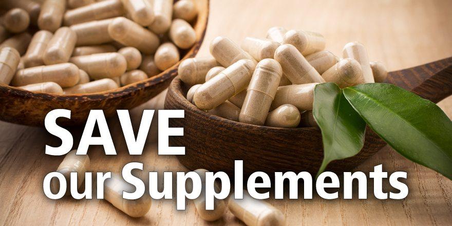 Alternative medicine tablets on a wooden spoon, green leaf.